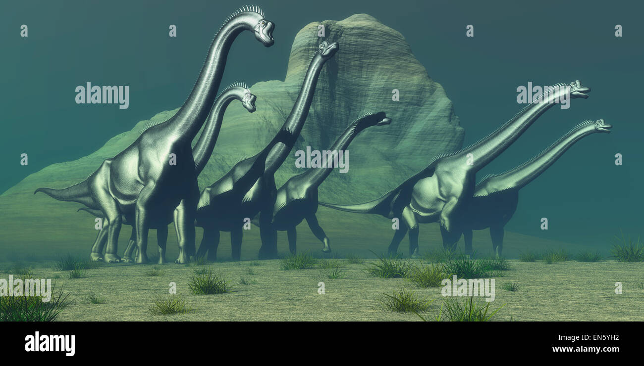 A herd of Brachiosaurus dinosaurs pass a high bluff in their search for a forest of trees for grazing. Stock Photo