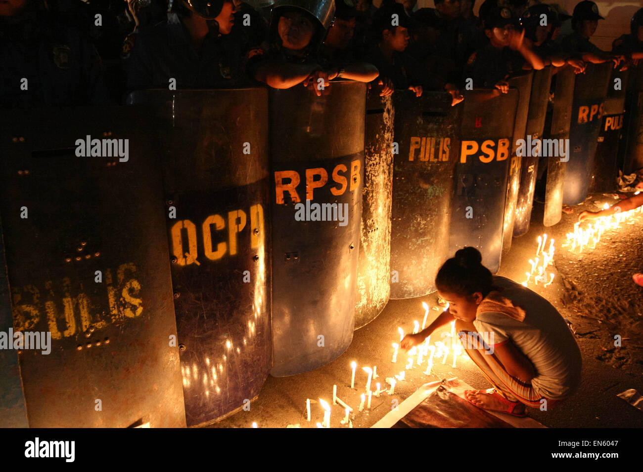 Makati, Philippines. 28th Apr, 2015. A young girl lights a candle in front of the police line outside the Indonesian Stock Photo