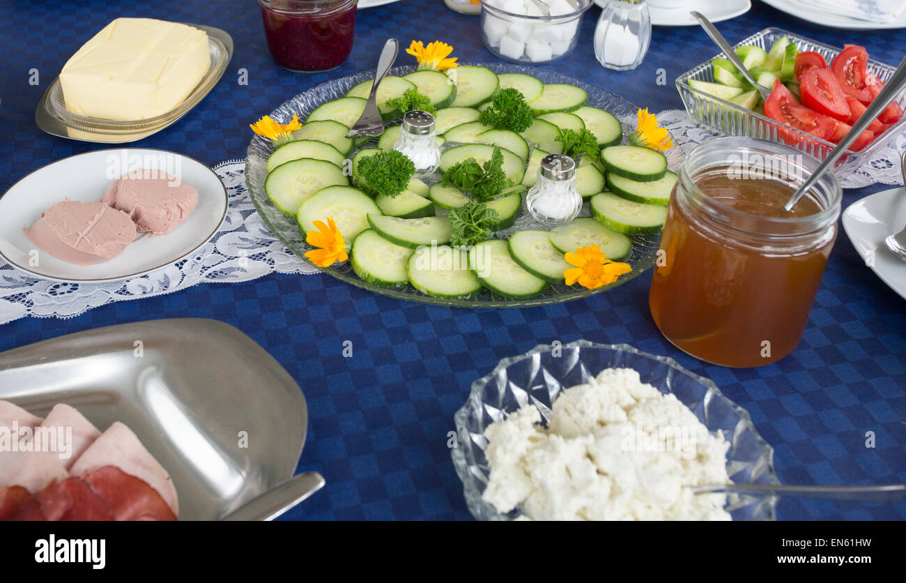 Luncheon table with platters of cold cuts, vegetables and other delicacies in Germany - Stock Image
