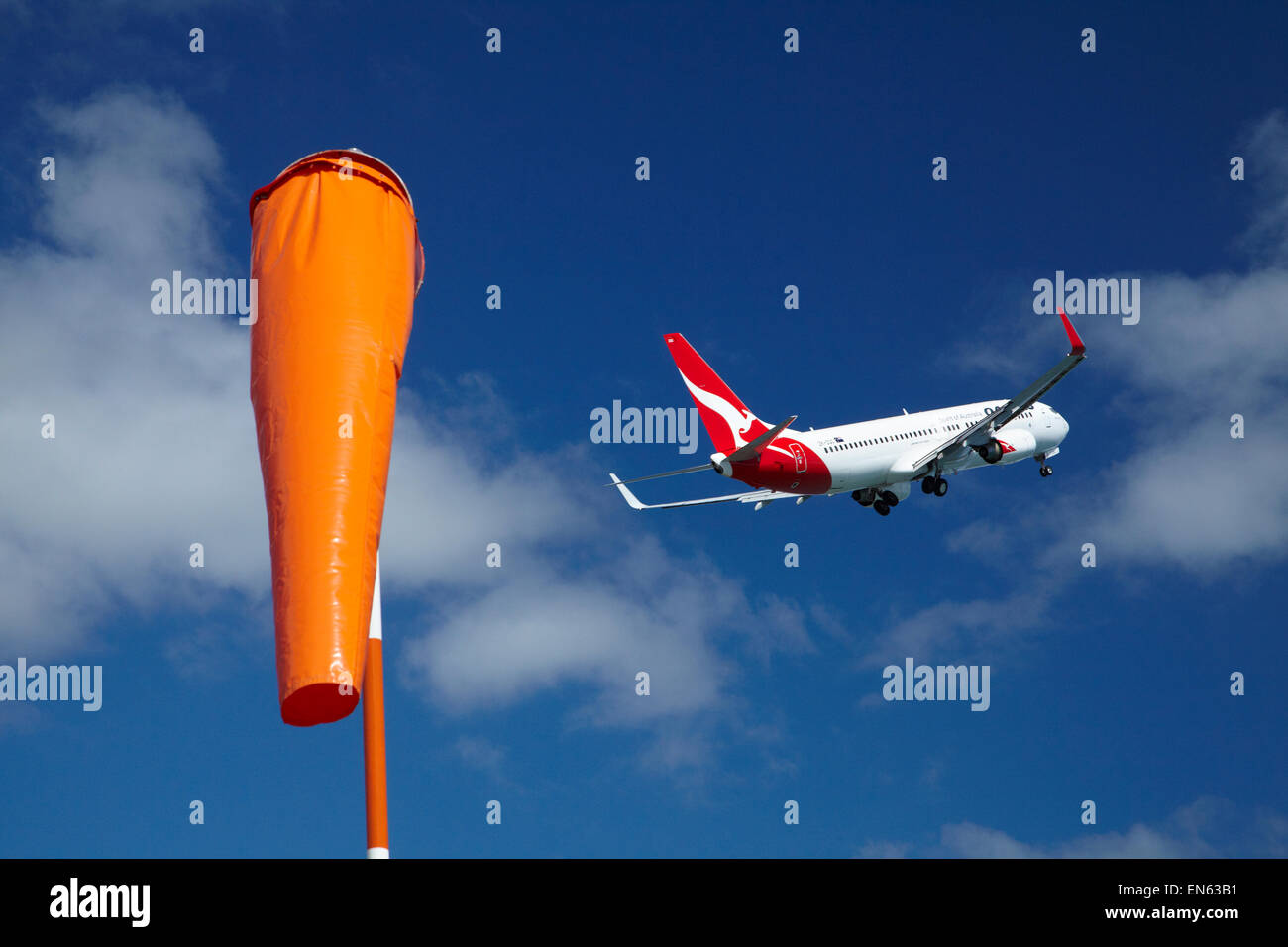 Wind Sock, and Qantas Boeing 737-800 taking off from Wellington International Airport, Wellington, North Island, - Stock Image