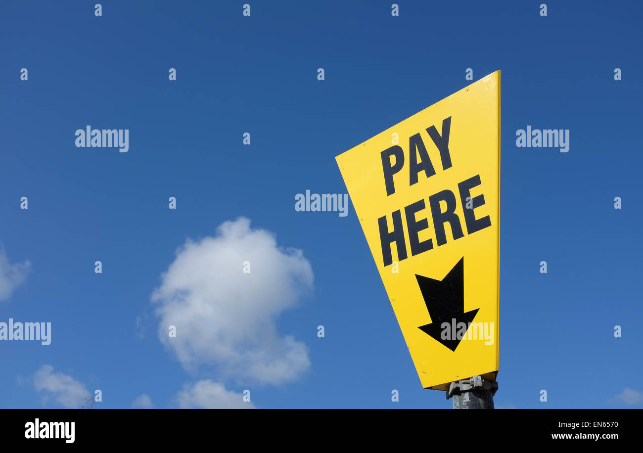 Yellow pay here sign against a blue sky background with copy space - Stock Image