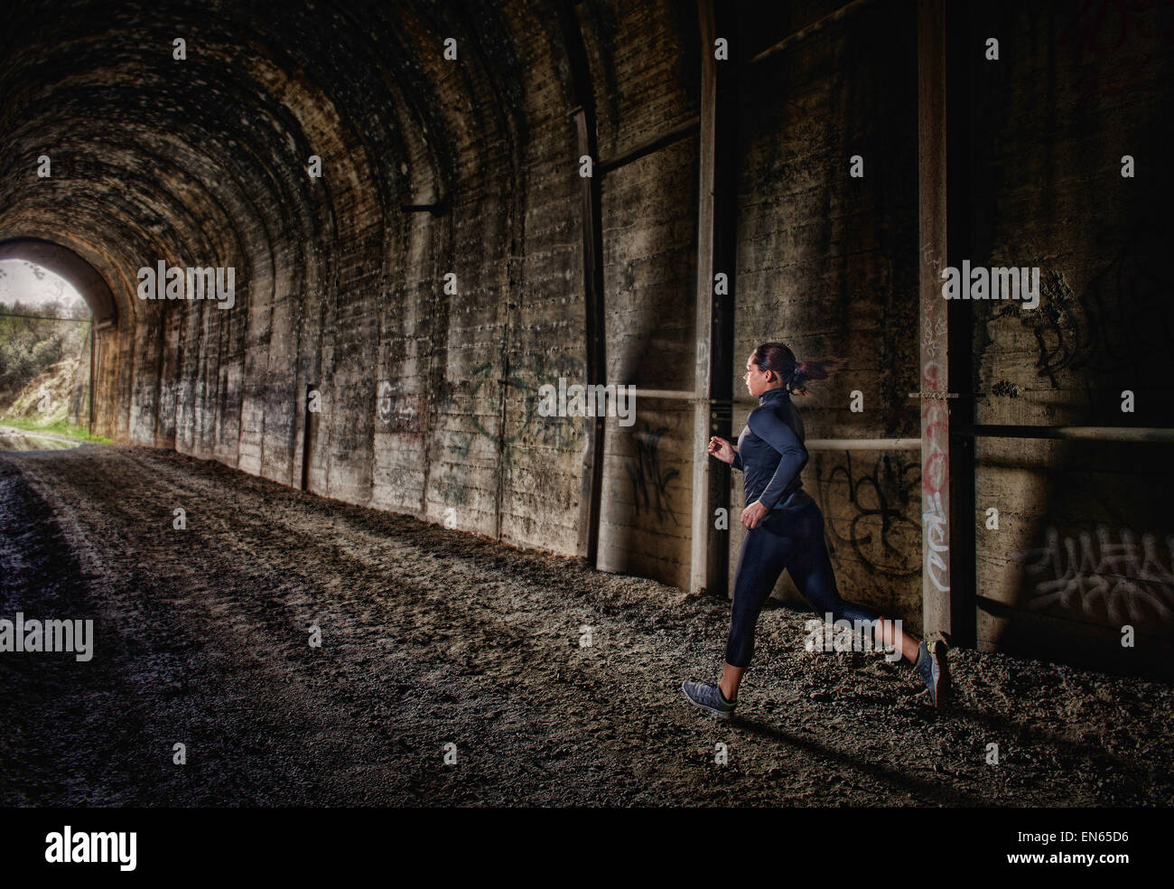A young woman running through a tunnel as part of her morning fitness routine. - Stock Image