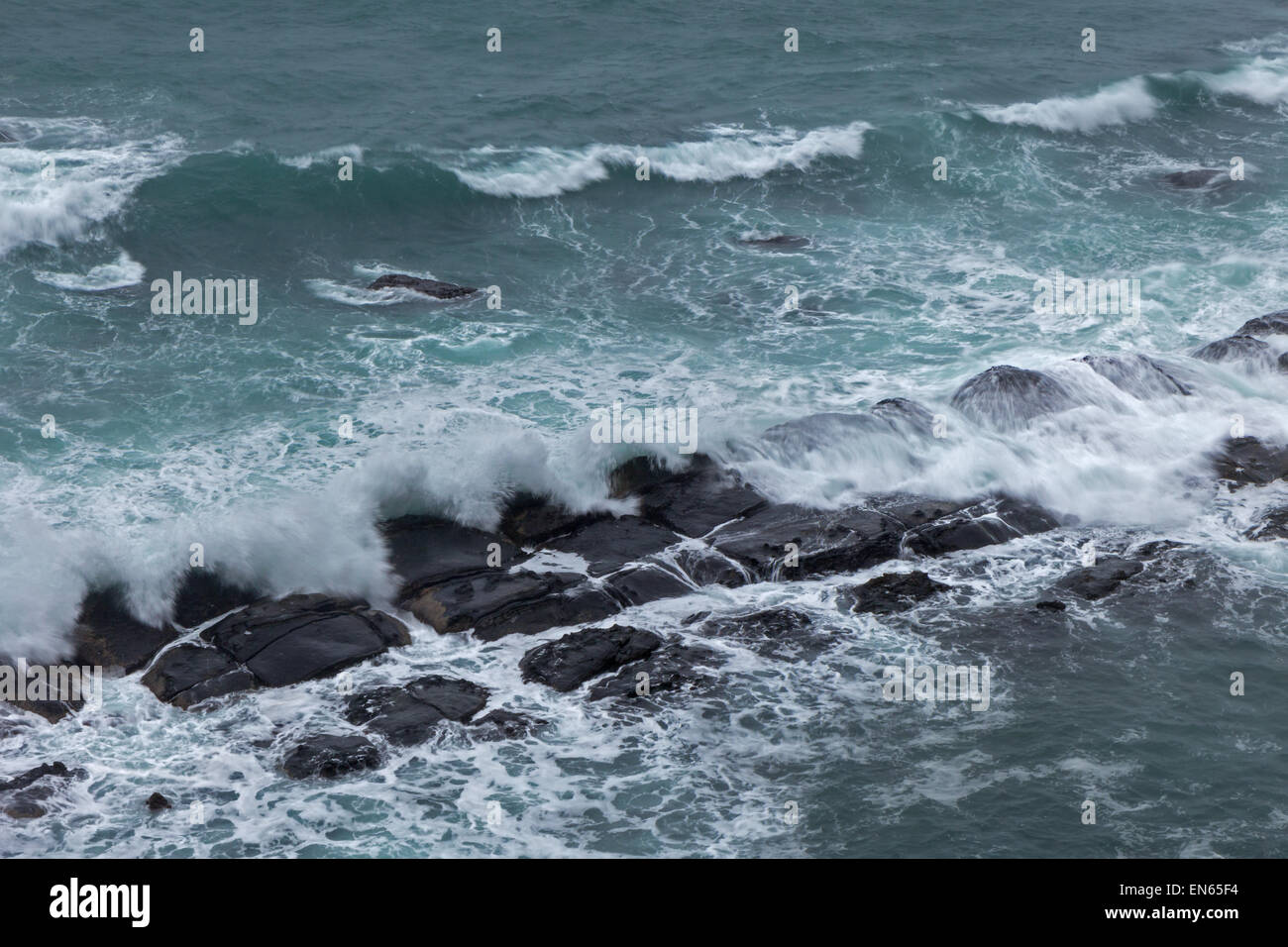 Waves crashing rocks  at an overcast day, viewed slightly from above - Stock Image