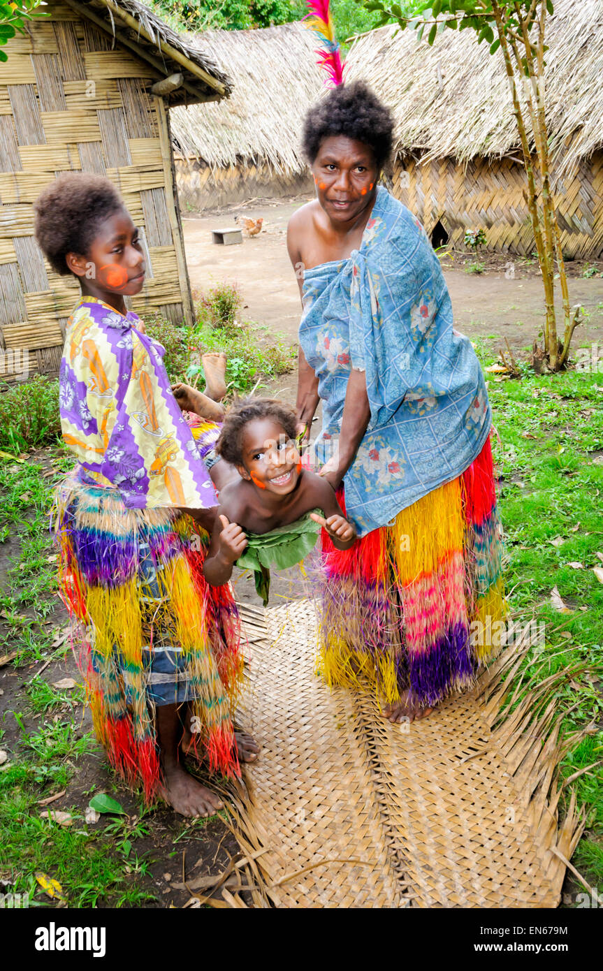 South Pacific Islander women demonstrating with a child a traditional stretcher made from leaves. Tanna, Vanuatu. - Stock Image