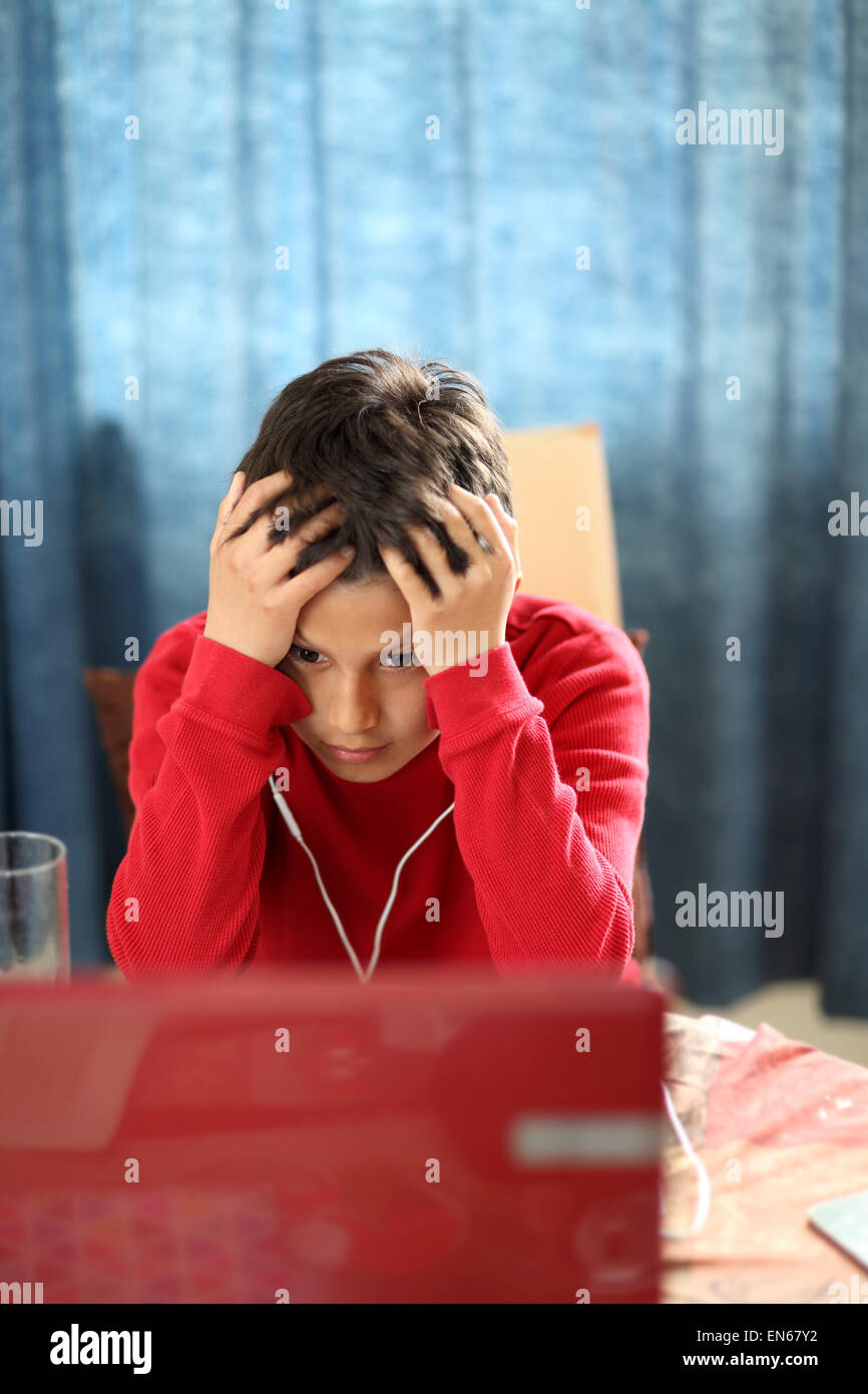 Young boy looks confused while doing his homework on a computer - with shallow depth of field - Stock Image