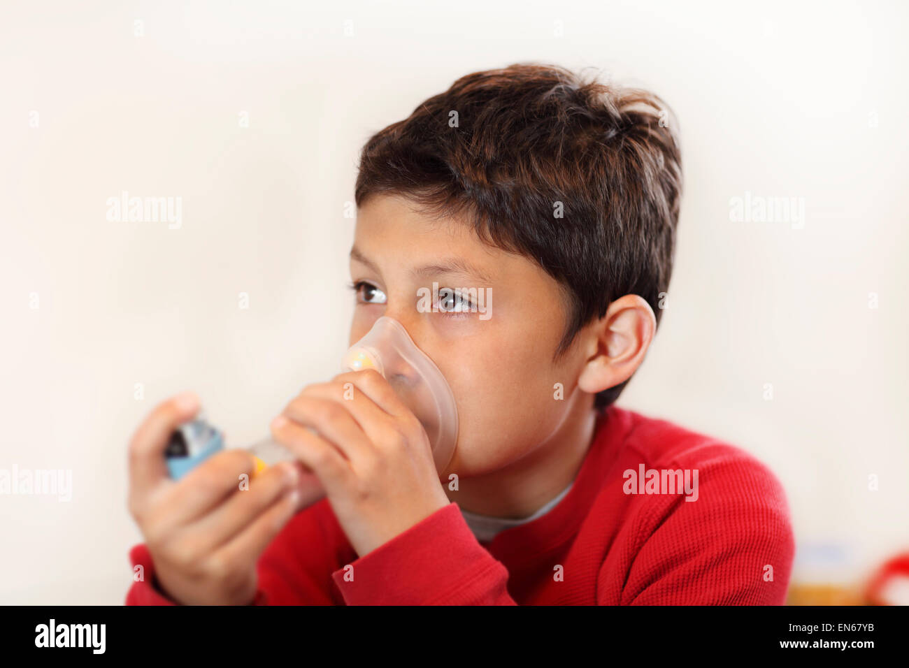 Young boy using inhaler on white background - with shallow depth of field - Stock Image