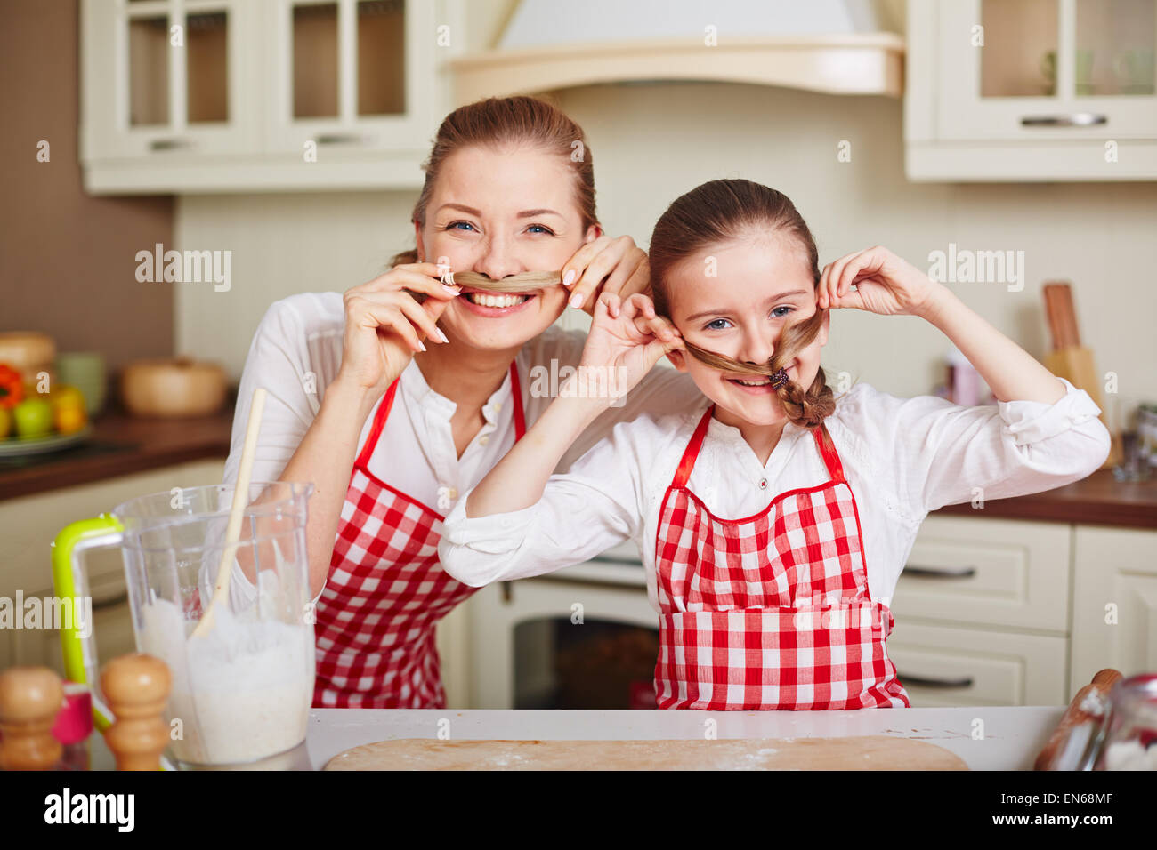 Ecstatic girl and her mother in aprons keeping ends of their pigtails by noses - Stock Image