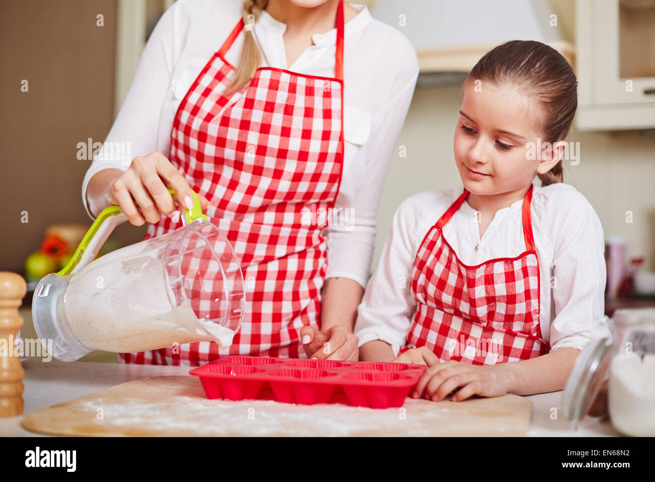 Curious girl looking at her mother filling in muffin forms with liquid dough - Stock Image