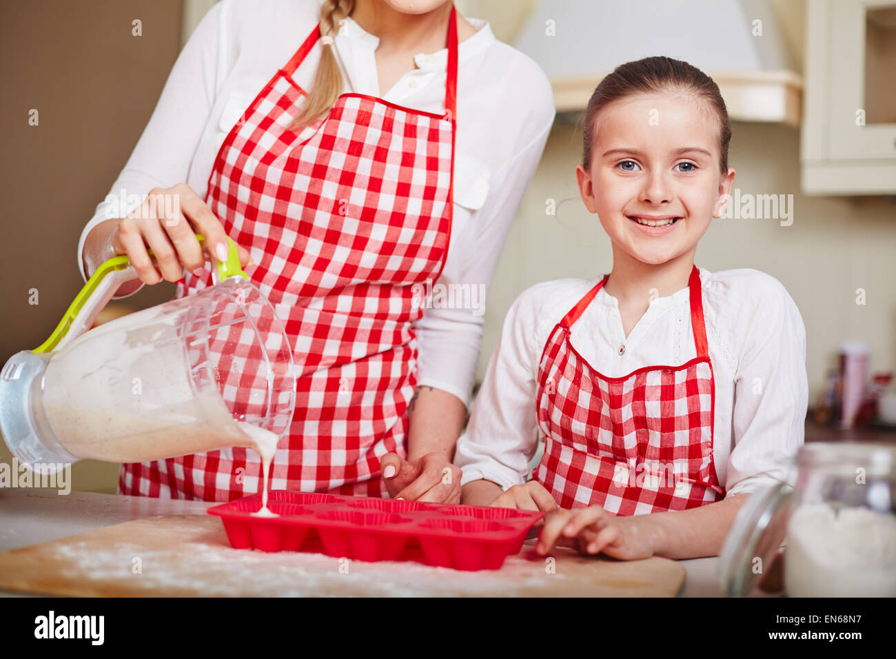 Adorable girl looking at camera while her mother filling in muffin forms with liquid dough - Stock Image