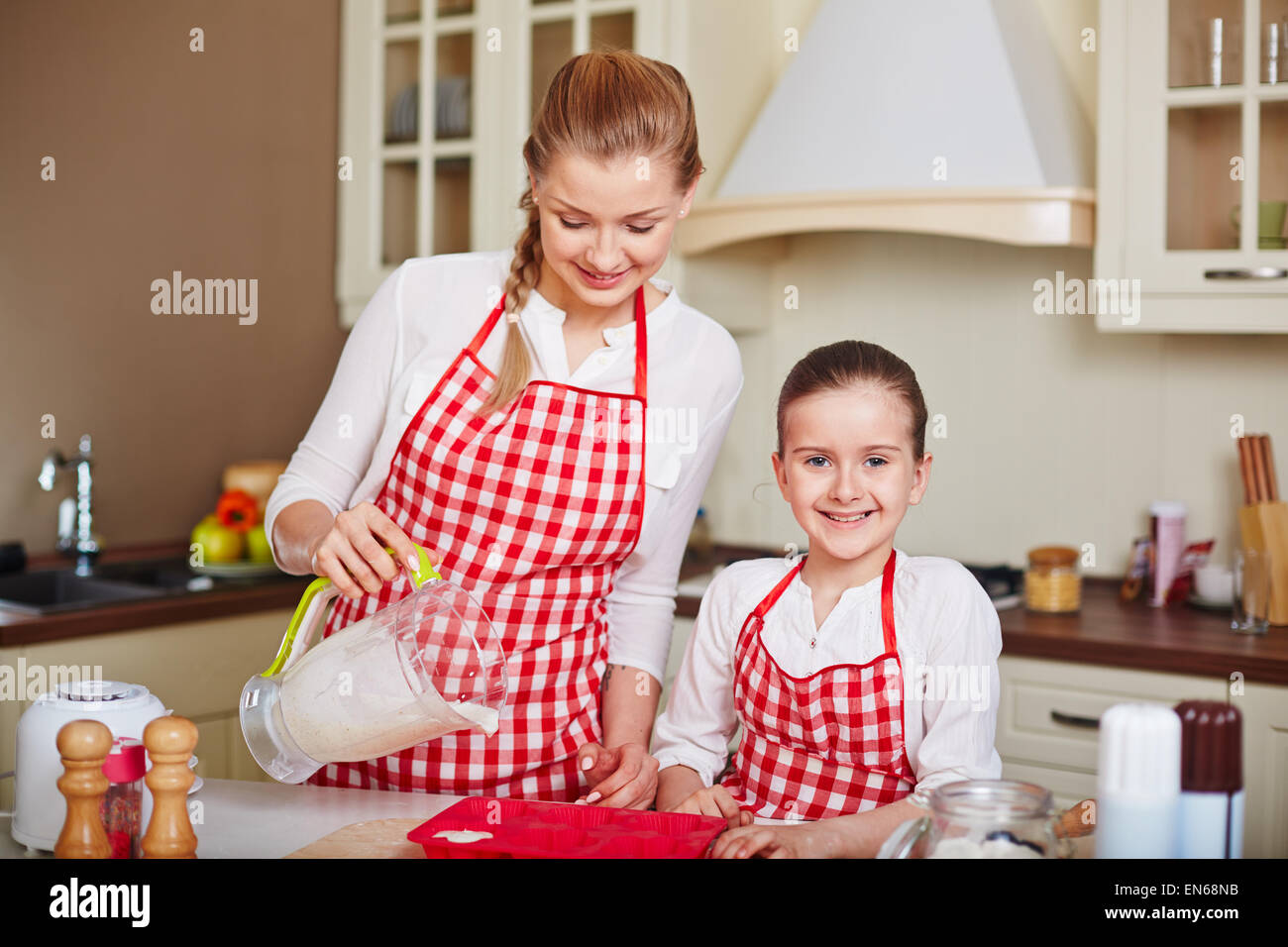 Adorable girl and her mother filling in muffin forms with liquid dough near by - Stock Image