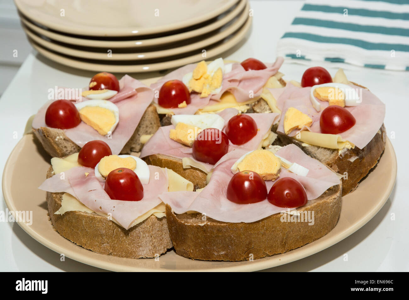 Sandwiches with egg, cheese, ham and cherry tomatoes. Food and drink theme. Stock Photo