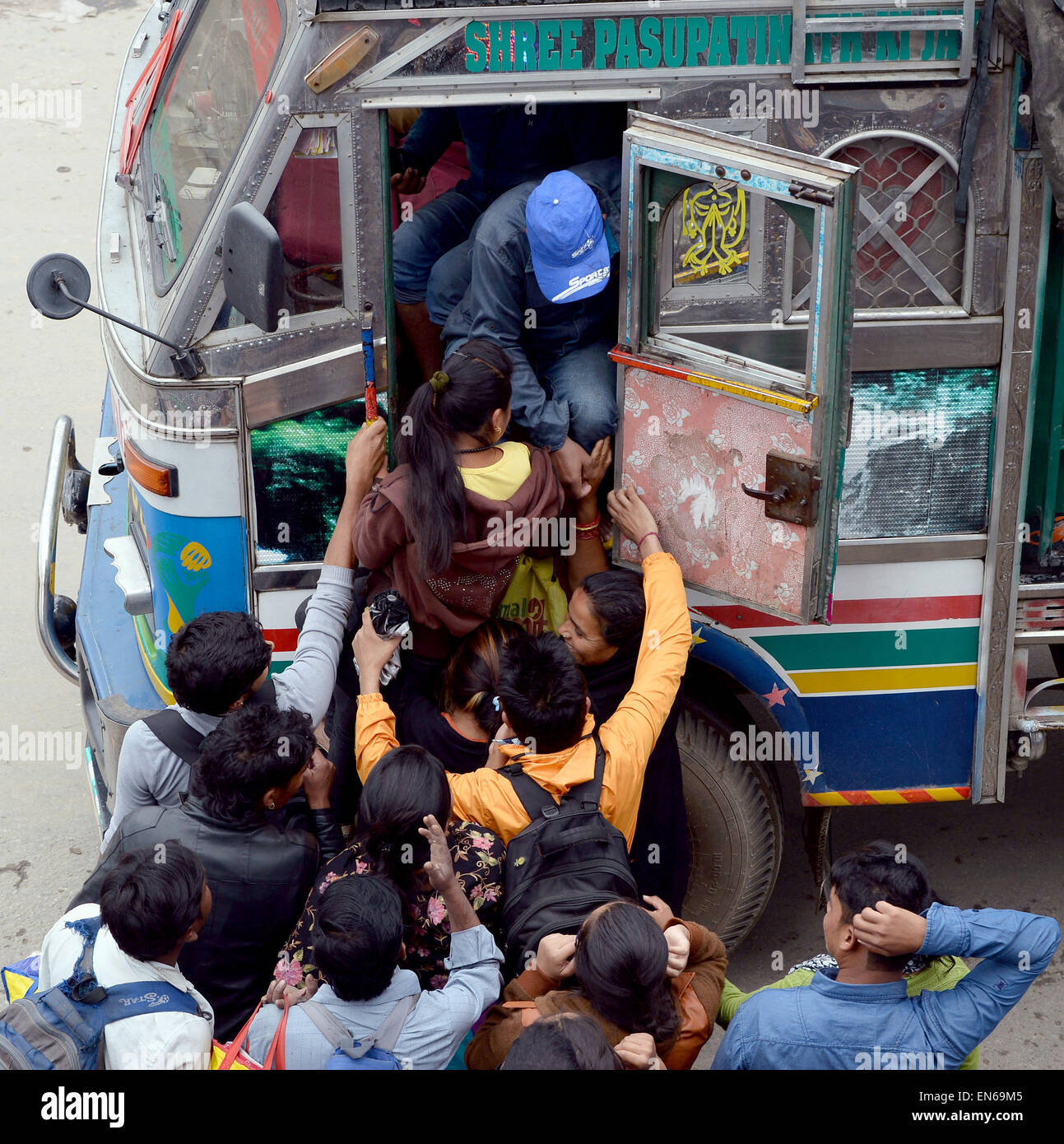 Kathmandu, Nepal. 28th Apr, 2015. People fight for a few available seats to get into a relief truck at Kalanki Chowk - Stock Image