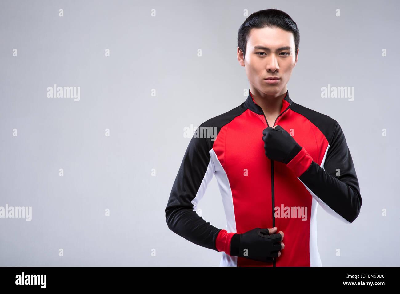 Young man zipping sportswear - Stock Image