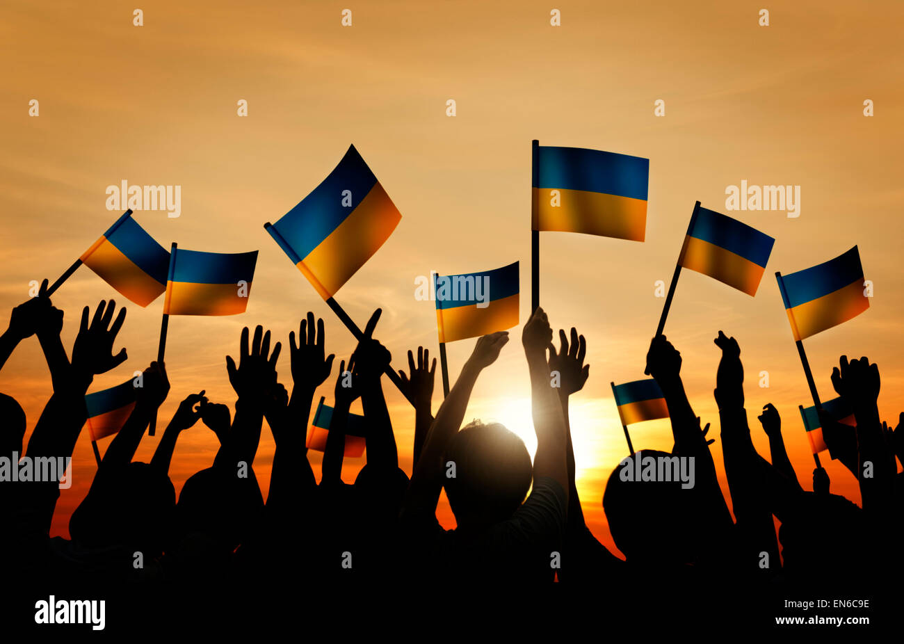 Group of People Waving Ukranian Flags in Back Lit - Stock Image