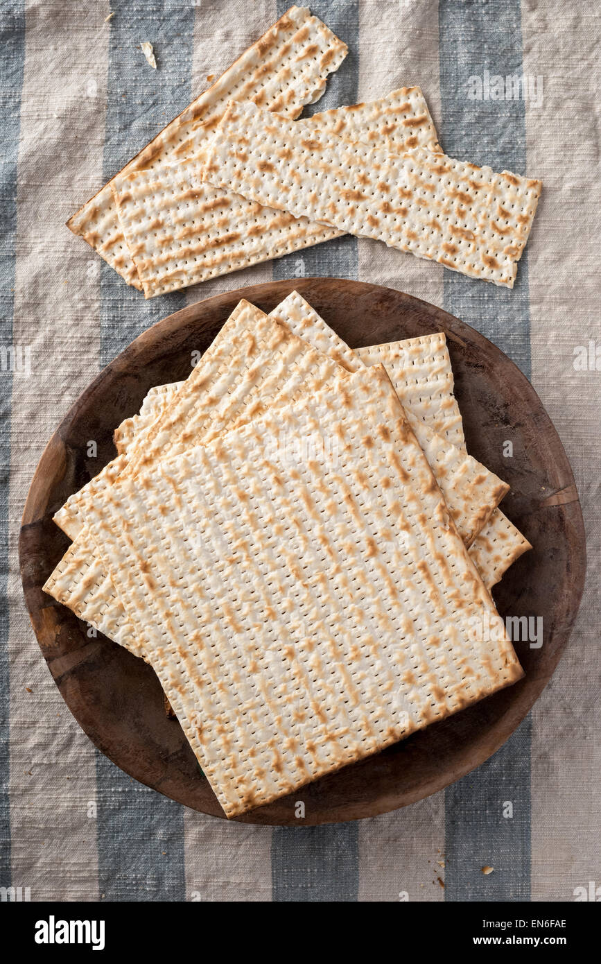 Matzah,  the unleavened bread used in the Jewish holiday passover, set on wood bowl in rustic setting - Stock Image