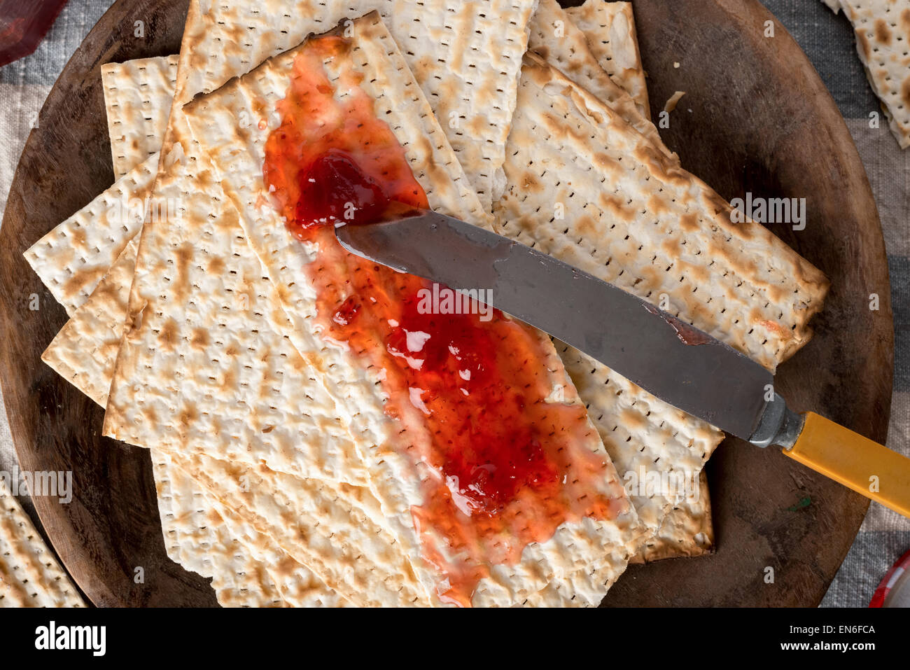 Matzah, served here with strawberry preserves,  the unleavened bread used in the Jewish holiday passover, set on - Stock Image