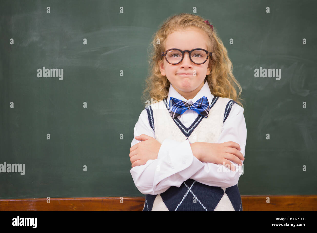 Perplex pupil looking at camera with arms crossed - Stock Image