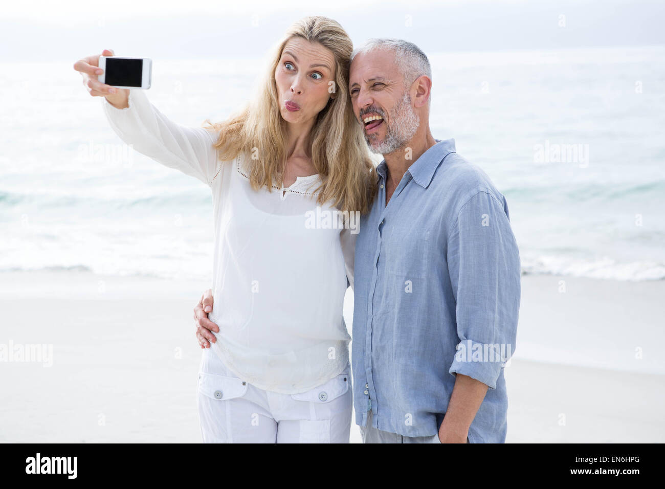 Happy couple taking selfie with mobile phone - Stock Image