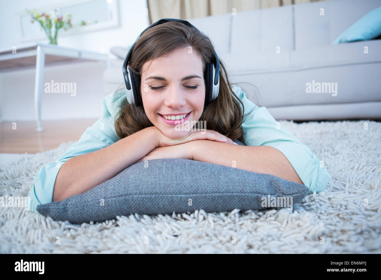 Peaceful woman listening musing lying on the floor - Stock Image