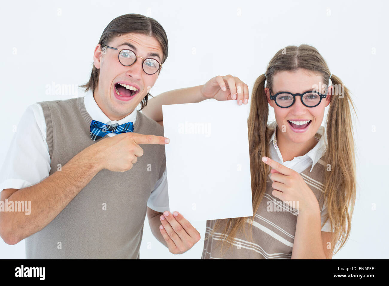 Geeky hipsters pointing at poster - Stock Image