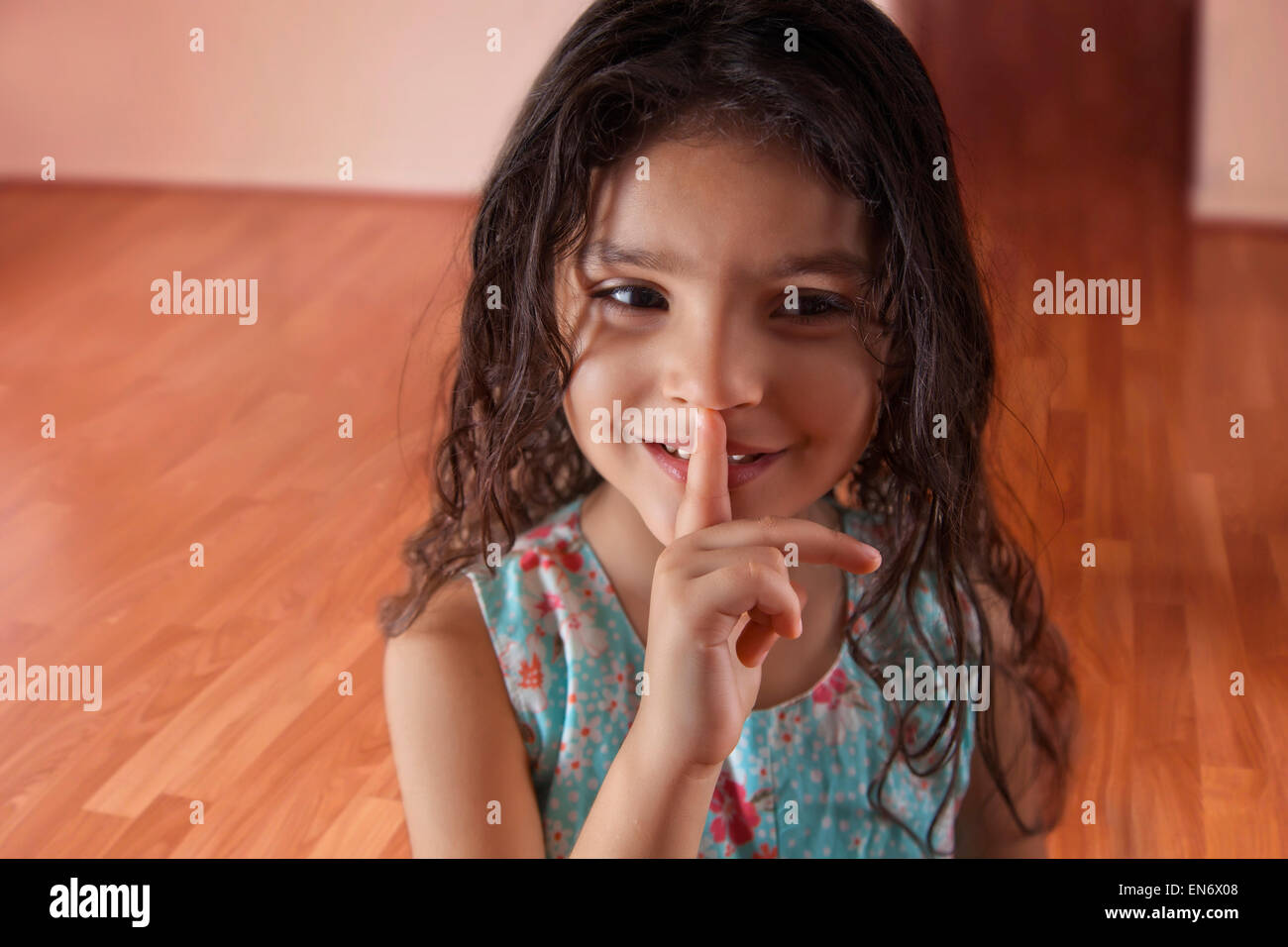 Little girl with finger on lips - Stock Image