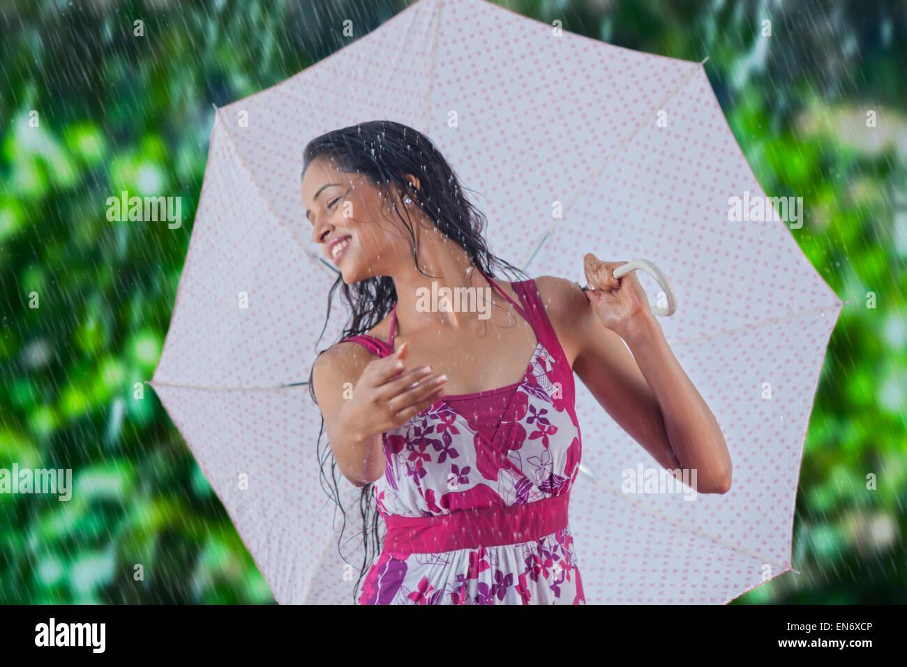 Woman with umbrella enjoying the rain Stock Photo