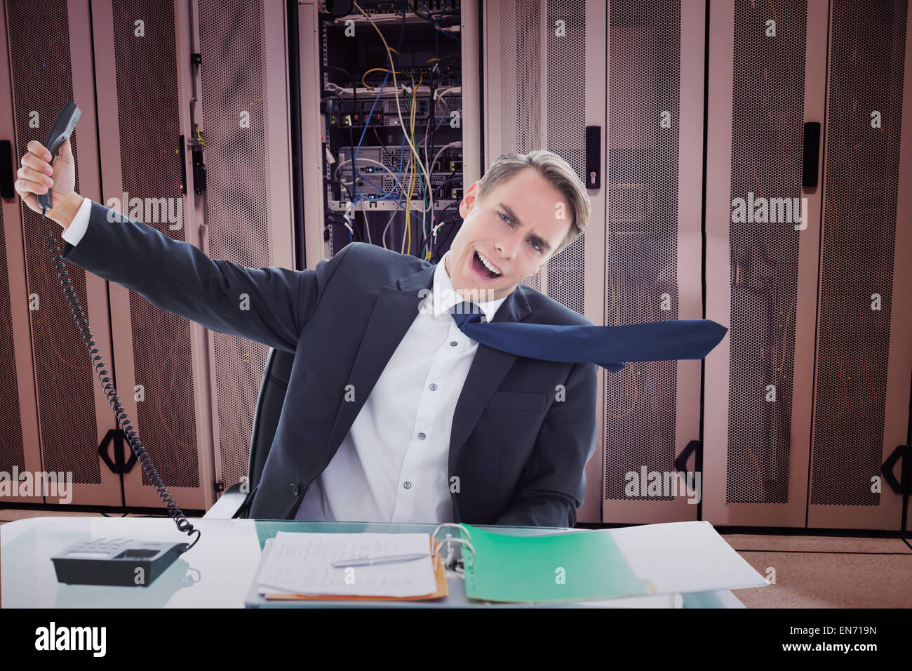 Composite image of businessman shouting as he holds out phone - Stock Image
