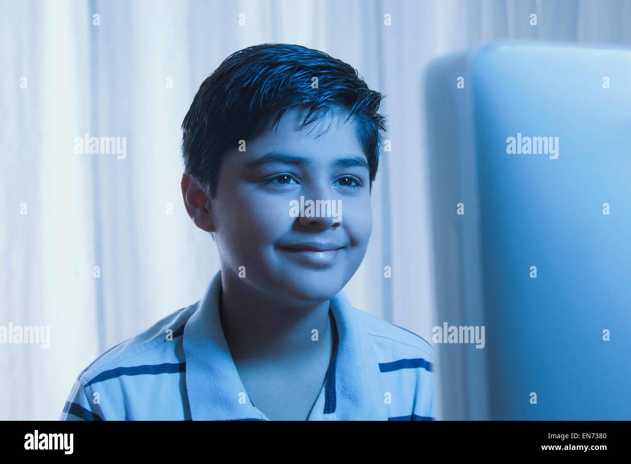 Young boy looking at a computer monitor - Stock Image