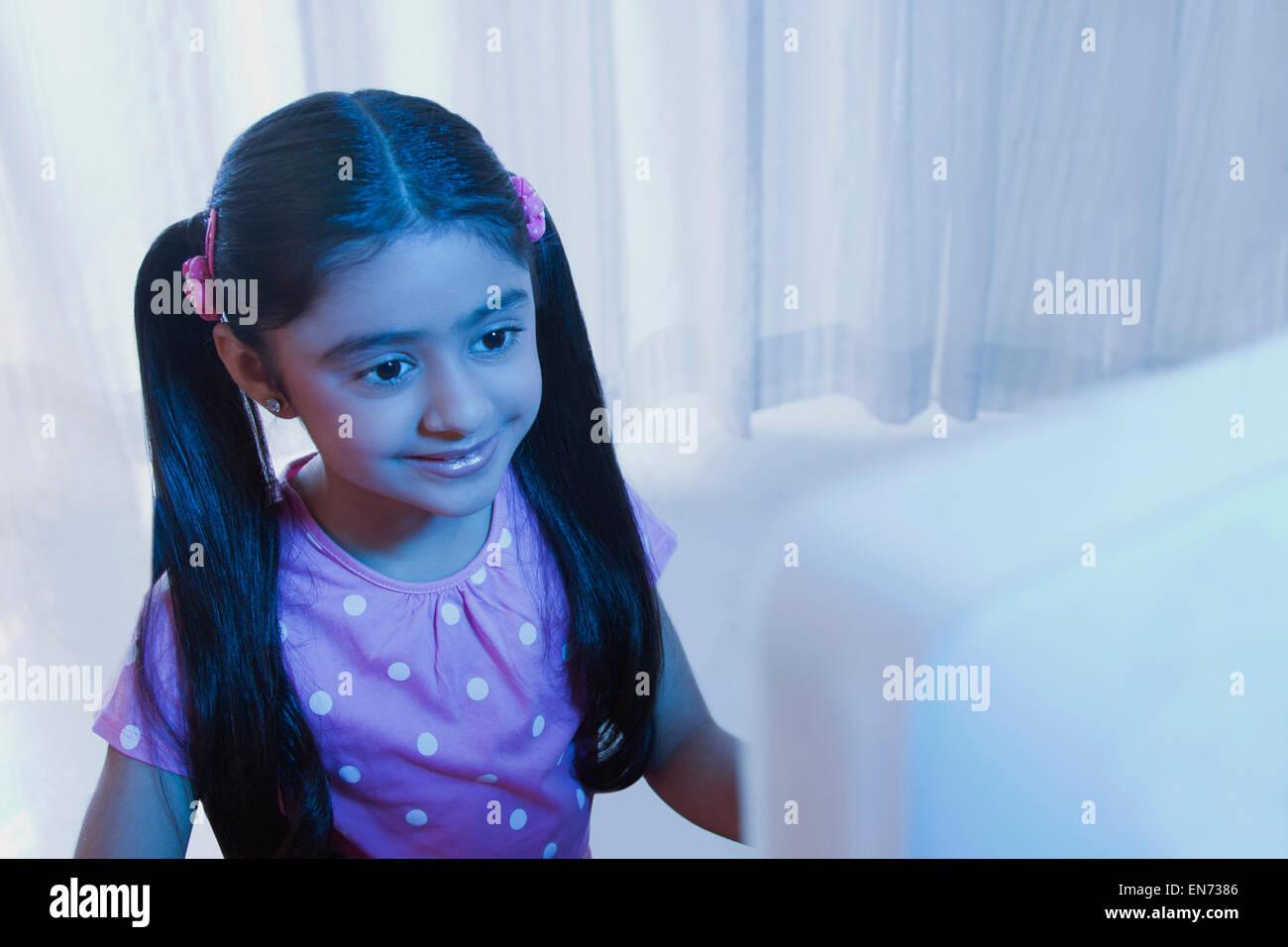 Young girl looking at a computer monitor - Stock Image