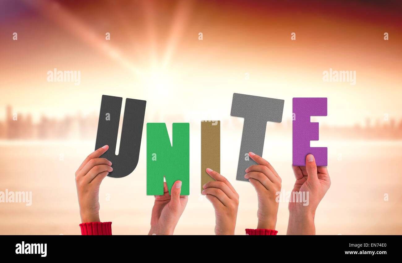 Composite image of hands holding up unite - Stock Image