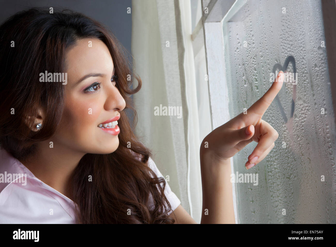Woman drawing heart on window Stock Photo
