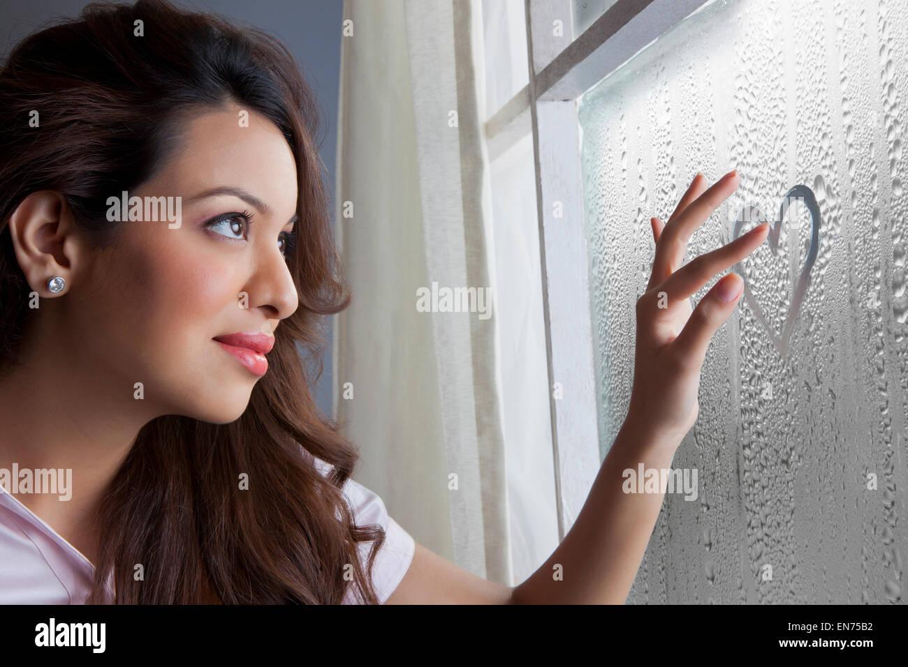 Woman drawing heart on window Stock Photo