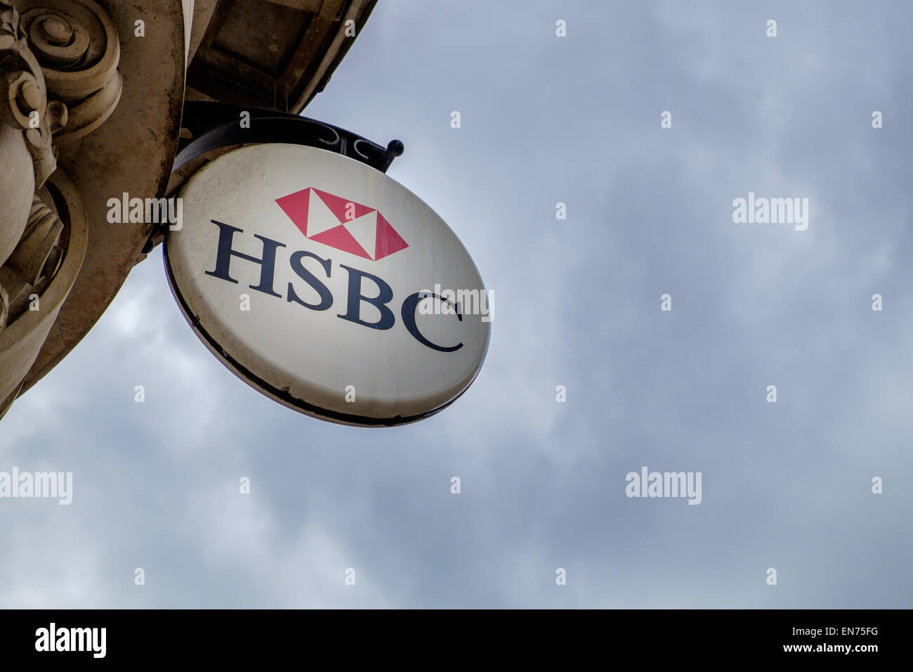 A HSBC sign above the Cirencester main branch of the bank, shot against a gloomy, cloudy sky economy forecast concept - Stock Image