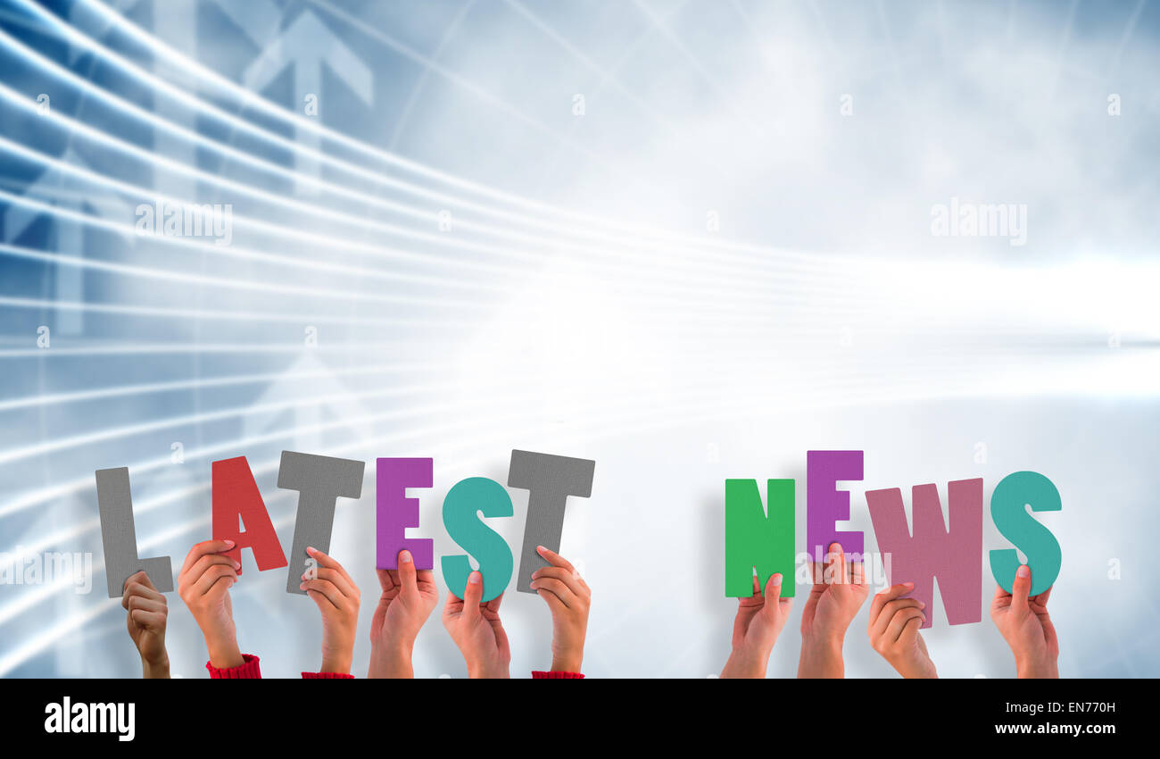 Composite image of hands holding up latest news - Stock Image