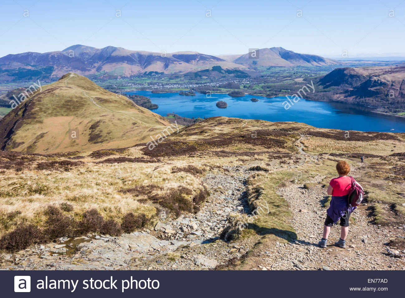 A walker pauses on the way up to Maiden Moor to take in the view of Catbells, Derwentwater and the distant hills - Stock Image