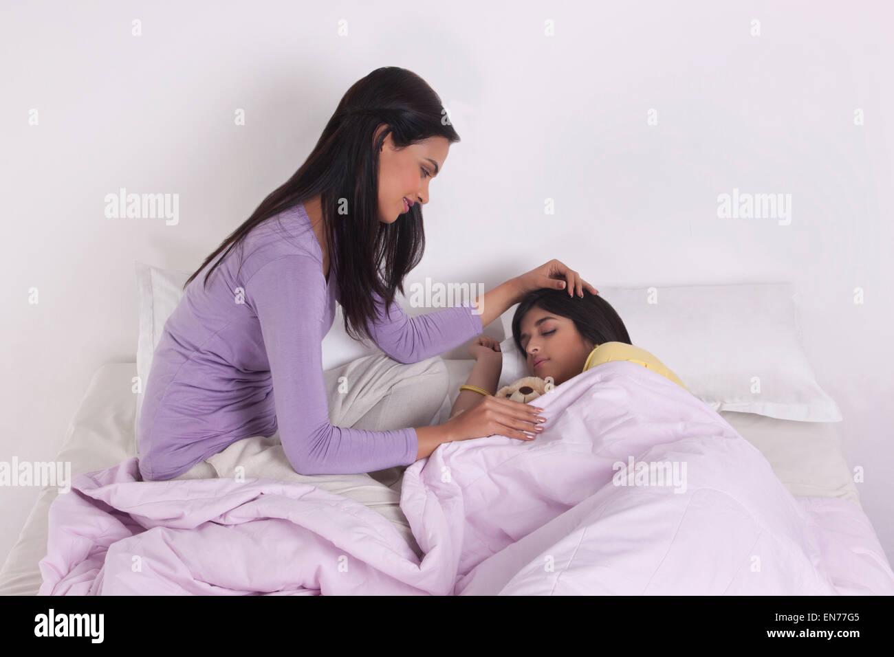 Elder sister watching younger sister sleeping - Stock Image