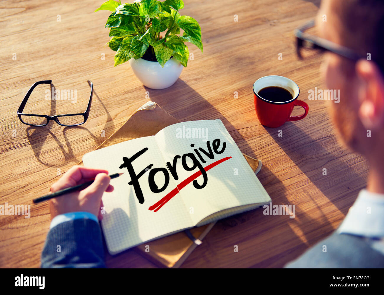 Man with Note Pad and Forgive Concept - Stock Image
