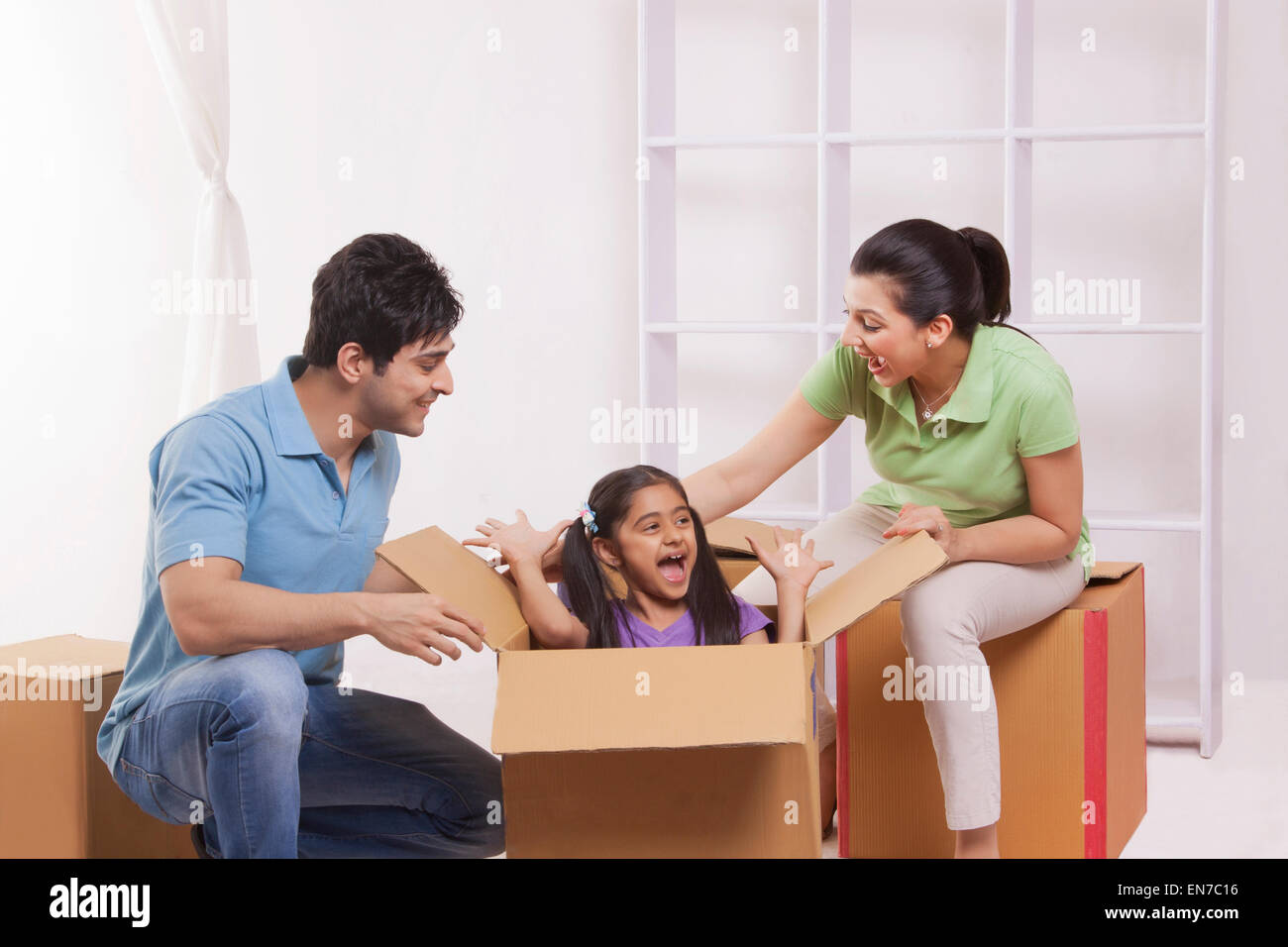 Girl playing hide and seek with parents - Stock Image