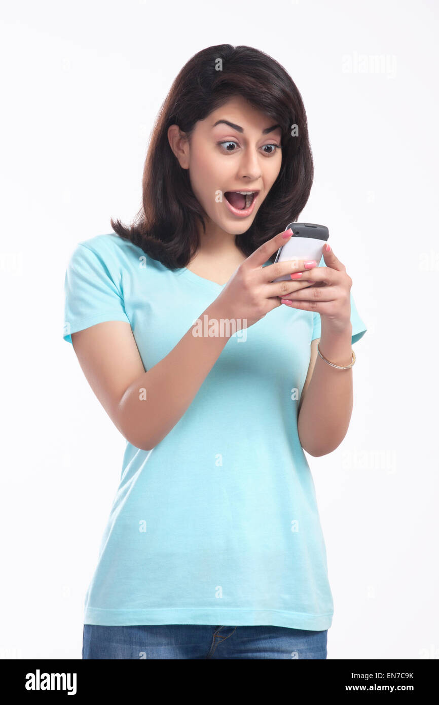 Woman surprised after reading sms - Stock Image