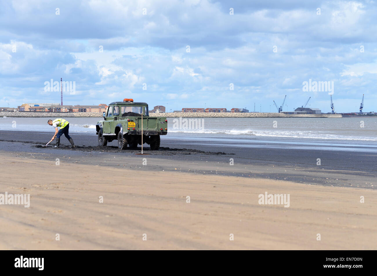 Man collecting sea-coal on Seaton Carew beach near Hartlepool, UK - Stock Image