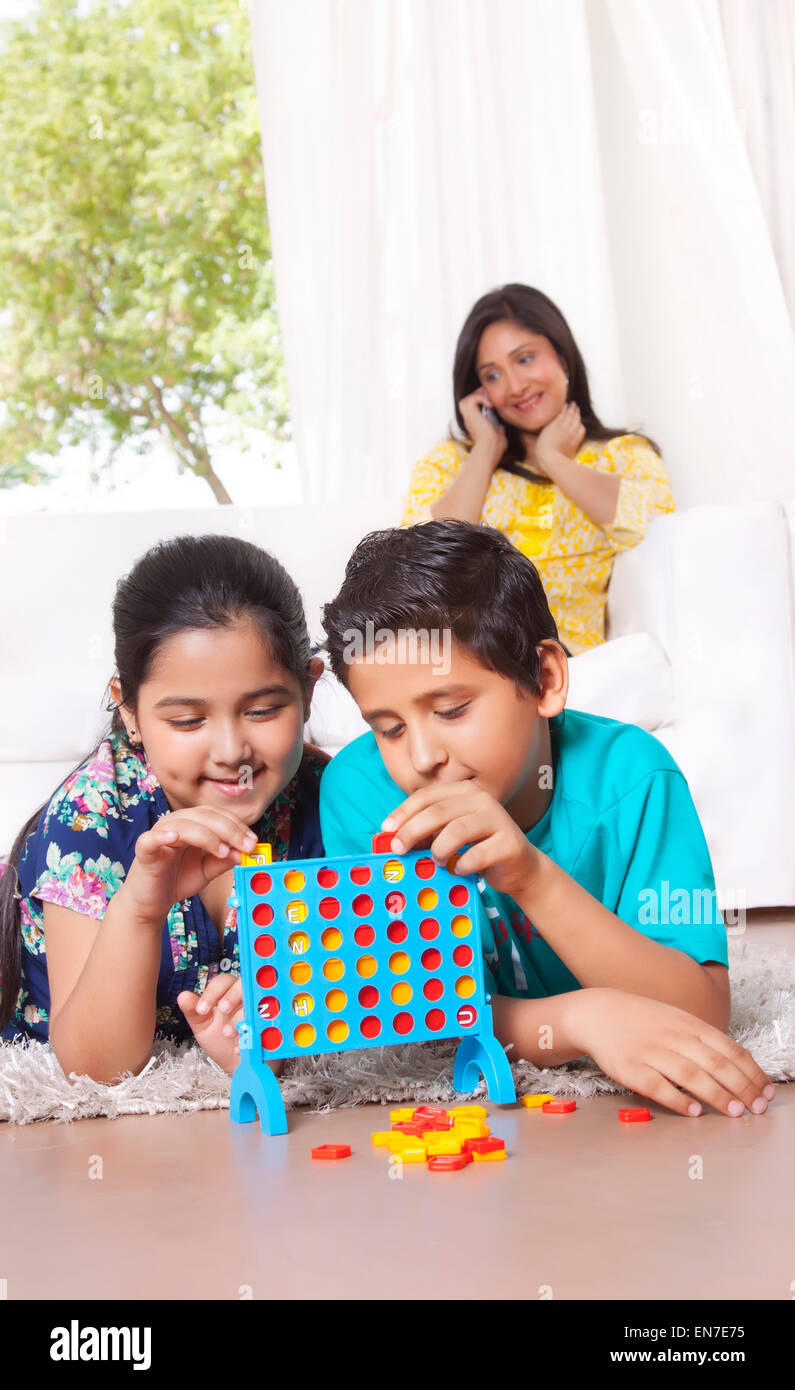 Kids playing while mother talks on mobile phone - Stock Image