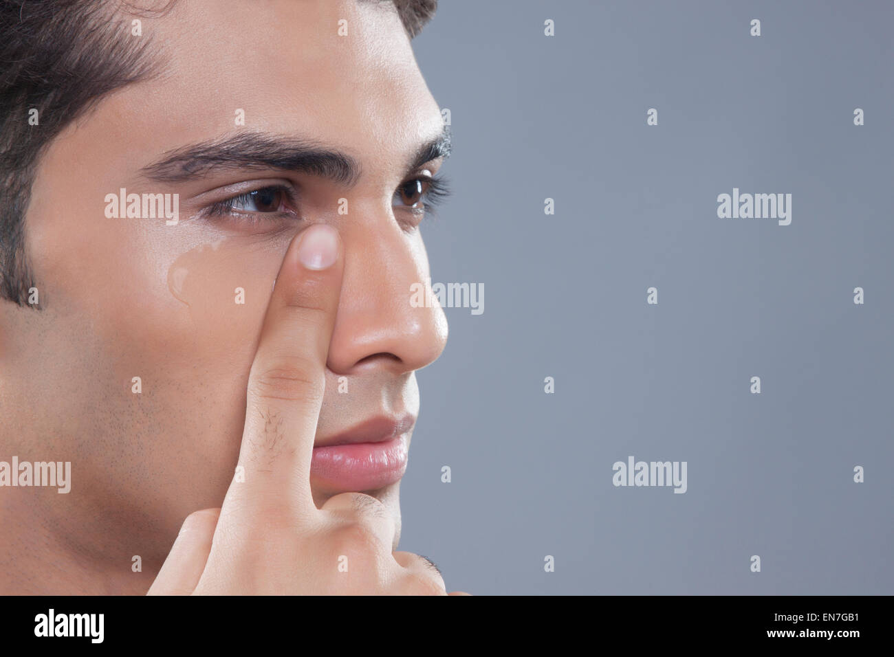 Young man putting on anti wrinkle gel - Stock Image