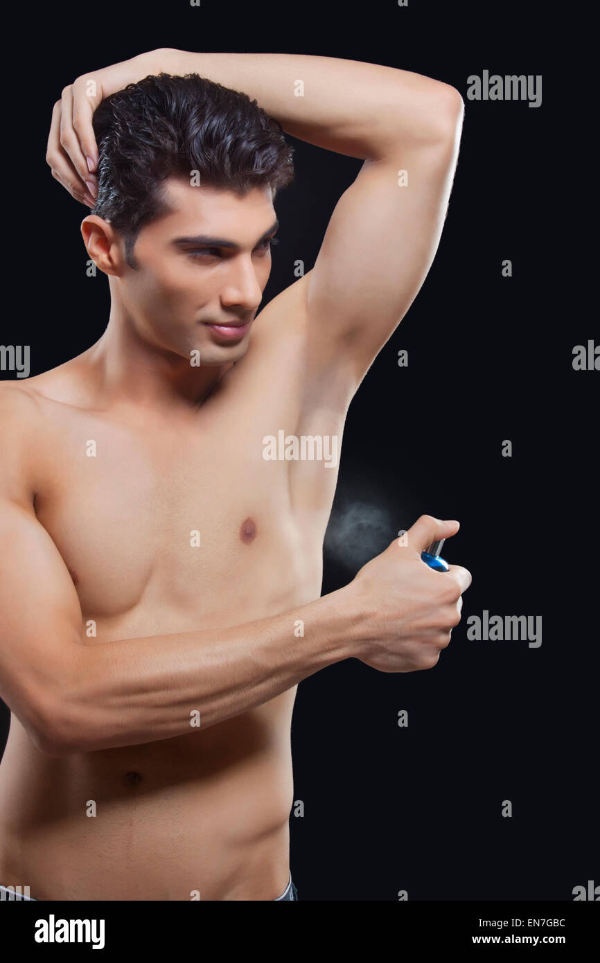 Young man spraying perfume on underarms - Stock Image