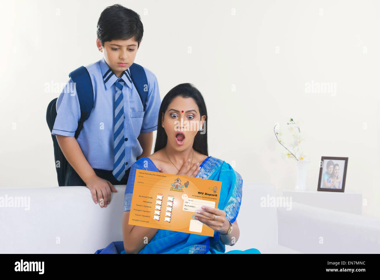 Mother shocked while looking at report card - Stock Image