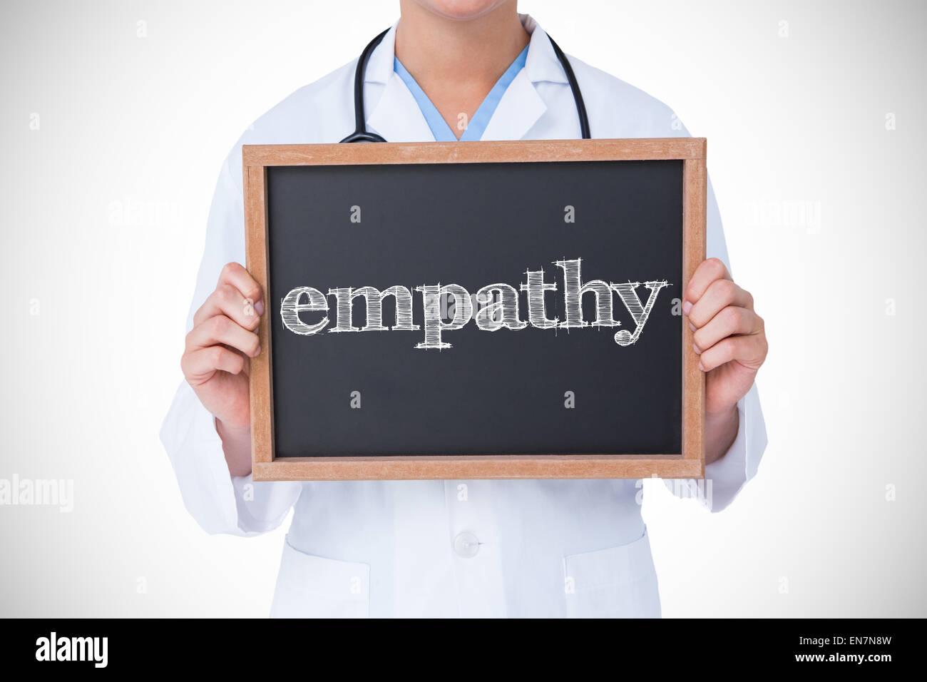 Empathy against doctor showing little blackboard - Stock Image