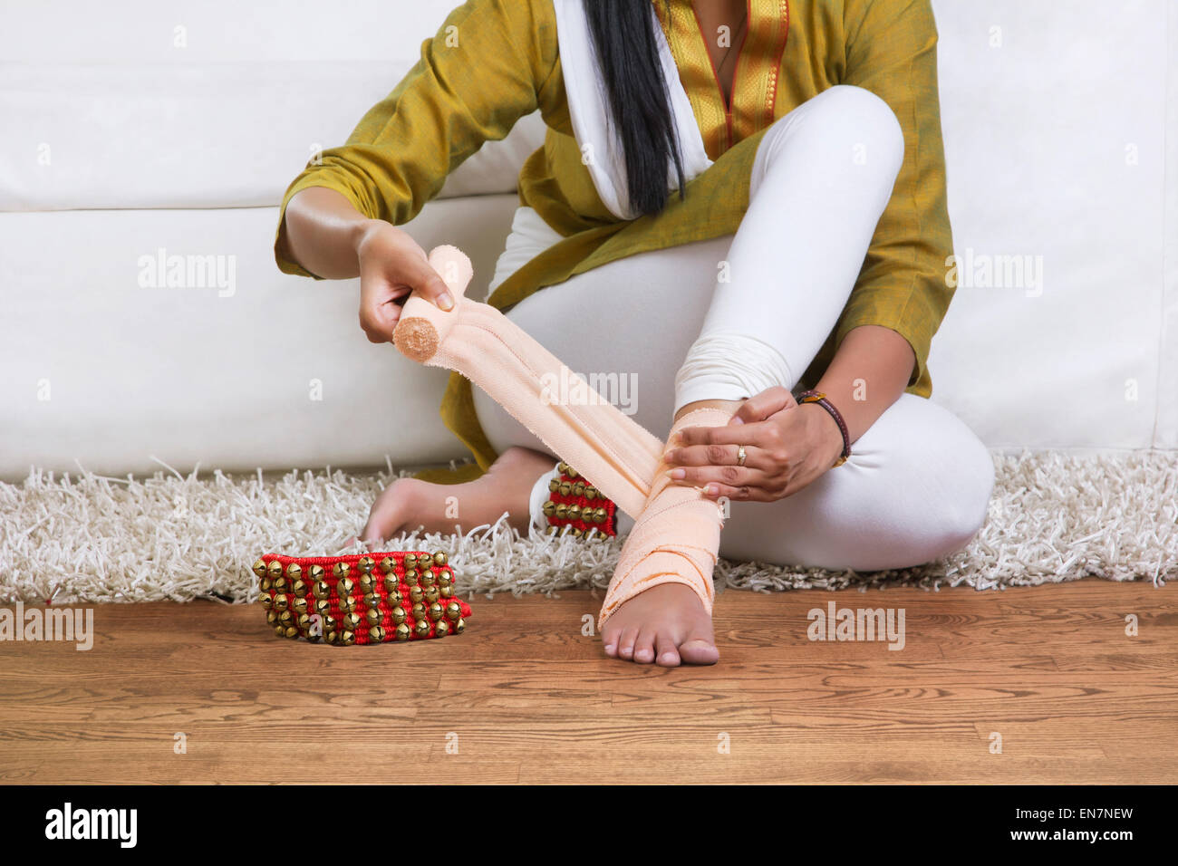Woman tying bandage around ankle - Stock Image