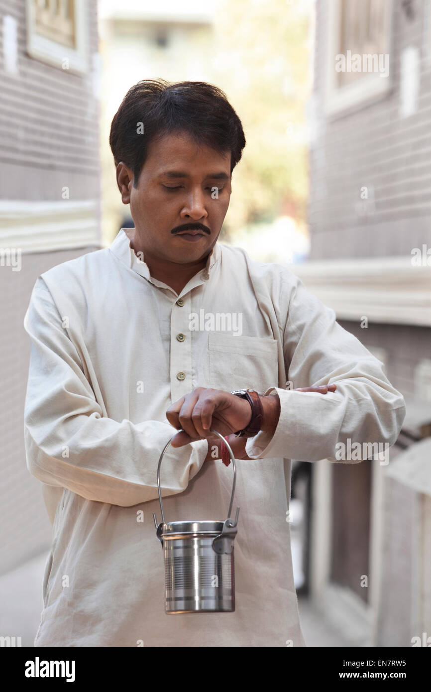 Man holding milk canister and looking at watch - Stock Image