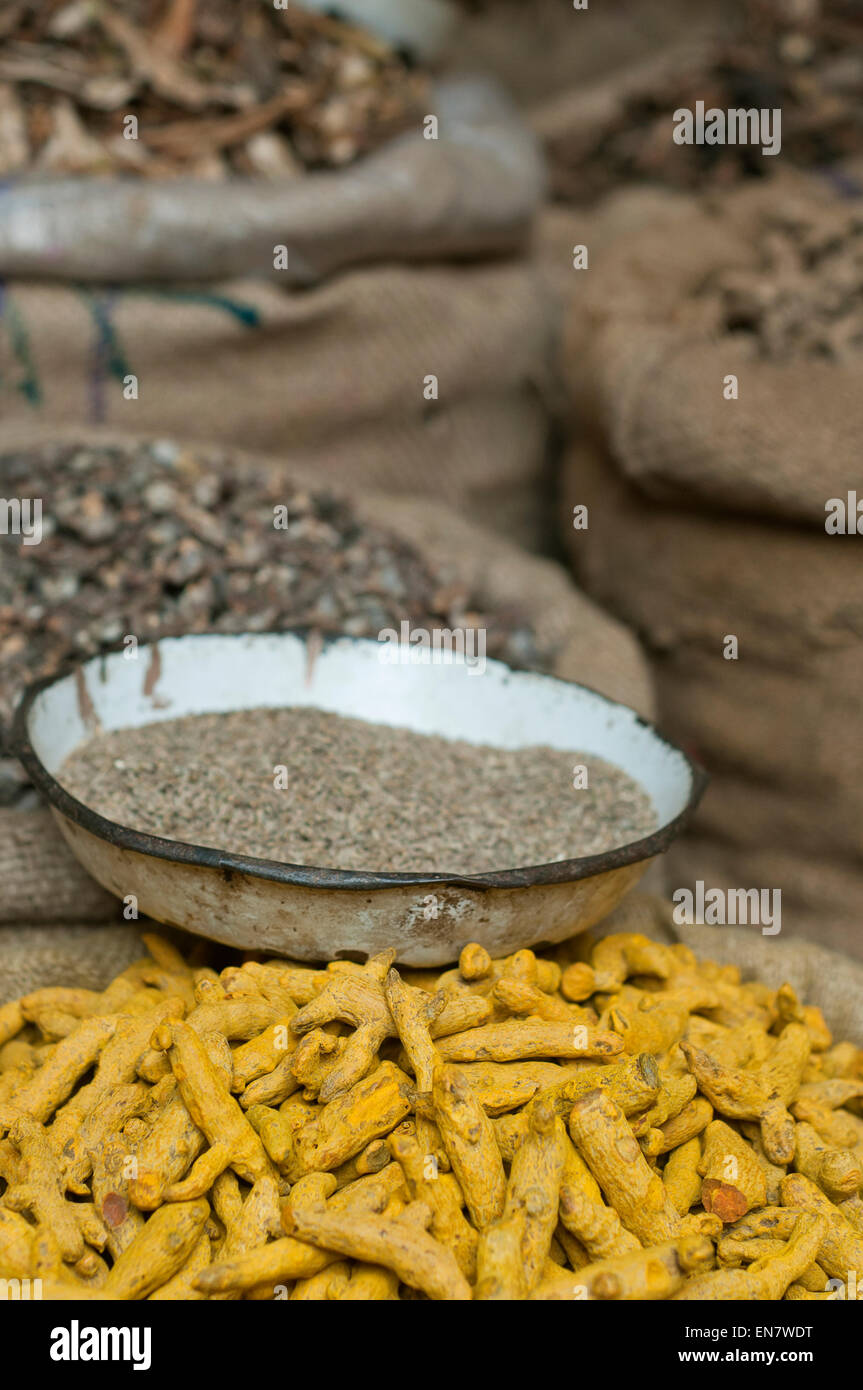 Sacks of turmeric root with jeera in bowl for sale at the market - Stock Image