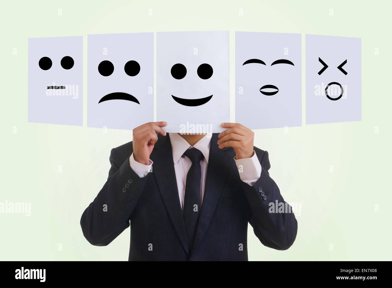 Businessman holding various emoticons - Stock Image