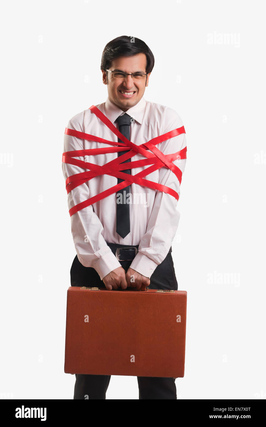 Businessman tied up with red ribbon - Stock Image